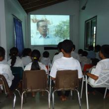 School children in Lveate Village watch filmed interviews with older villagers about their experience under the brutal Pol Pot regime.