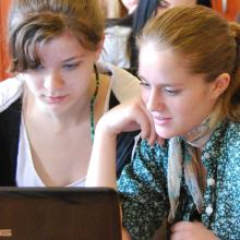 Two teenaged girls researching the internet on a desktop computer.