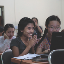 Smiling students with computers