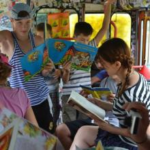 Children reading books inside the trolleybus.