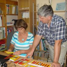 A librarian shows a farmer how to produce brochures.