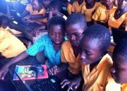 Three Ghanaian children, in orange school uniforms, in a classroom crowding around a computer.