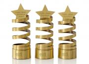 Three innovation award trophies - a golden spiral design, with a star on top.