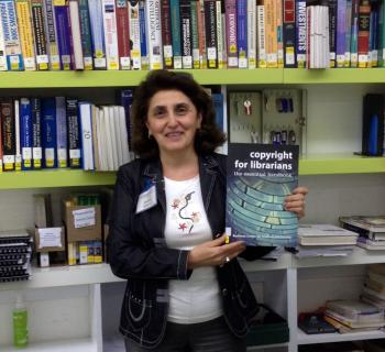 Full frontal photo of Hasmik Galystan, EIFL Copyright Coordinator in Armenia holding EIFL publication 'Copyright for Librarians'. Hasmik is standing in front of library shelves where she works at the American University of Armenia.