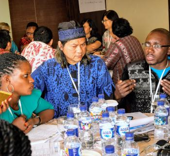 Young African librarians sharing ideas with Indonesian librarians, sitting around a table.