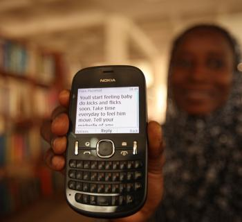 A mother shows a mobile phone with a text messages advising her about what to expect in pregnancy.