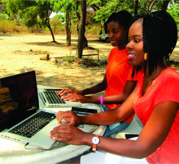 Two women using laptop computers outdoors, in a rural setting, to access their library's licensed e-resources.