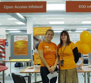 Photo of two Open Access Week organizers and speakers in Estonia standing in front of their booth.