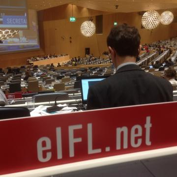 Close-up photo of EIFL's plaque at desk in WIPO's conference hall. The plaque is red with white text.