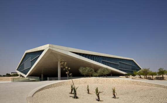 Qatar National Library building, photo from outside, showing driveway and triangular shape of building.