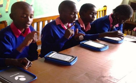 Children at a desk using kindles to read