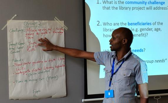 Raymond Chepkwony of Kenya National Library Service (KNLS) gives feedback from newsprint during group discussion.
