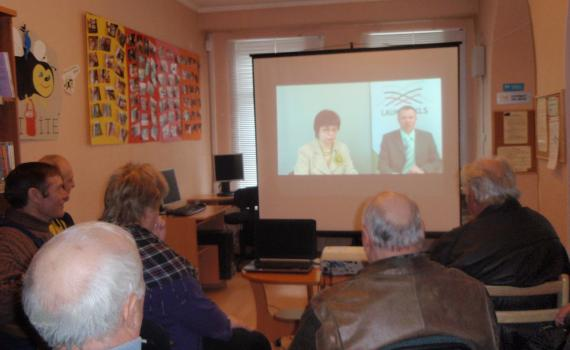 Farmers view a webinar in the library.