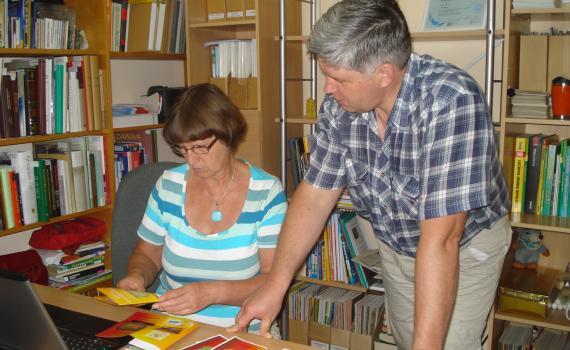 A librarian shows a farmer how to produce brochures.