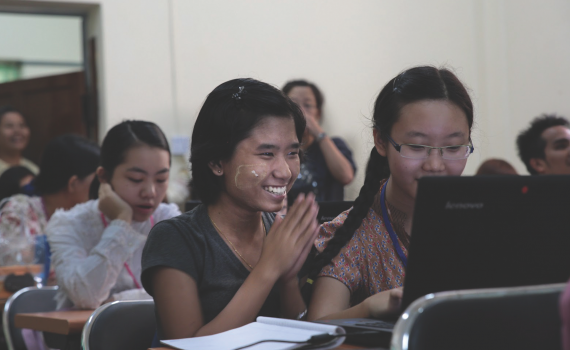 Smiling students learning to use computers in University of Yangon.